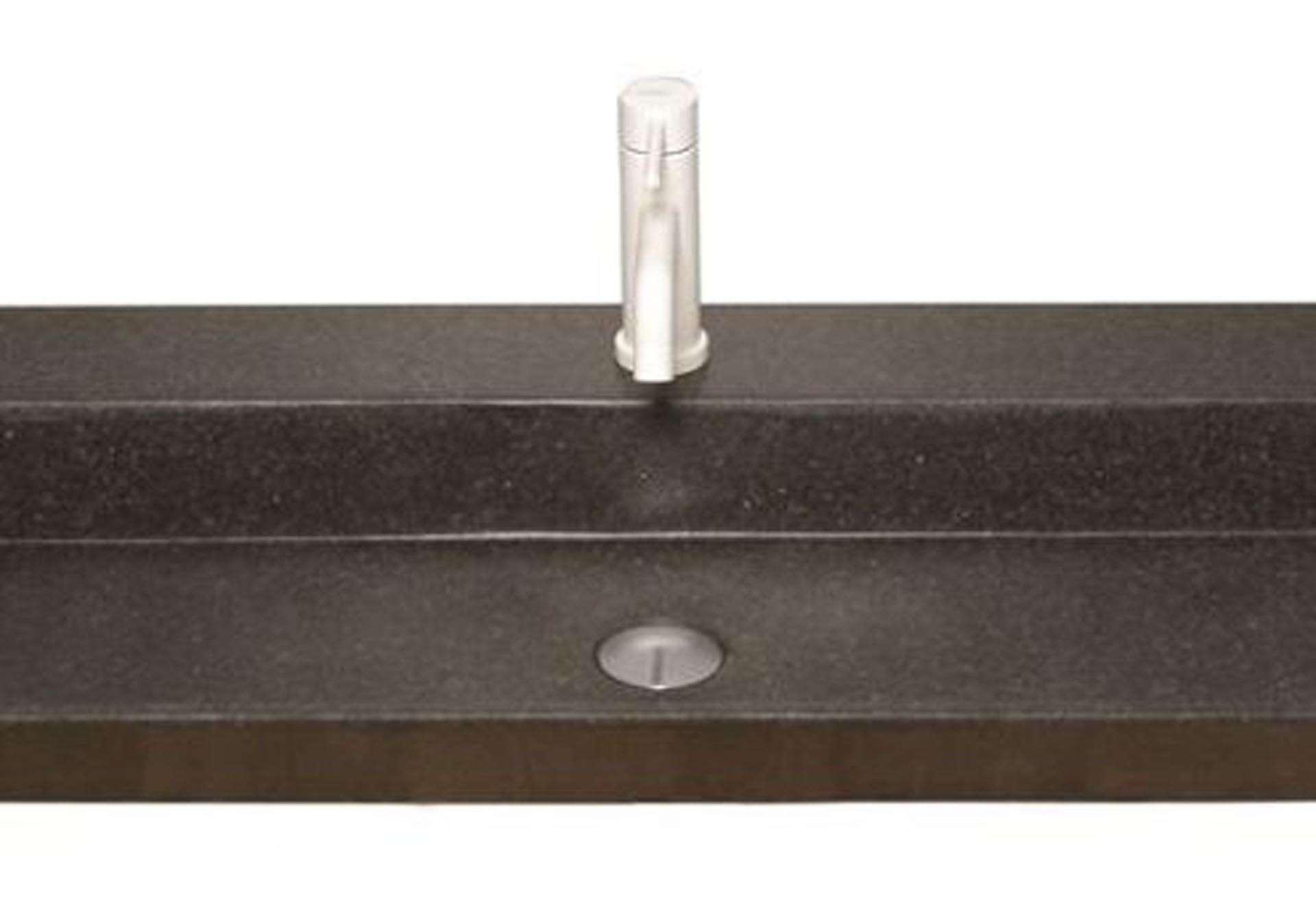 Eksklusiv designhåndvask fremstillet i massiv granit. Den sorte granit har en mat finish. En ægte stenvask i målene: 120,5 x 35,5 x 10 cm. Vasken er bearbejdet ud af et helt stykke granit - vi fræser ganske enkelt en håndvask ud af sten. Alle de afsluttende små detaljer er håndlavet. Med denne vask vil man få et stykke natur hjem i badeværelset. Det er kvalitet, som holder mange år ud i tiden. Vasken kan bruges som fritstående vask - da vasken er flad i bunden er den velegnet til at placere direkte på en bordplade. Vasken er hensynsmæssigt designet med fine rundinger, som både giver vasken et eksklusivt udtryk og gør den rengøringsvenlig. Vasken vedligeholdes med voks - vi anbefaler en behandling med vores egen naturvoks ID12002 et par gange om året for at opnå optimalt look.