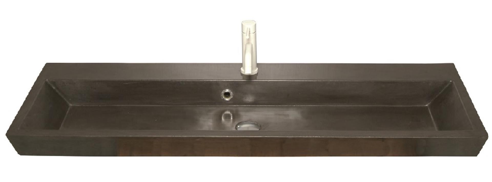 Lækker og simpel beton håndvask, med pæne afrundinger. Farven er i koksgrå - en fantastik flot og moderne betonfarve, der passer ind i ethvert badeværelse. Beton tåler ikke stærke rengøringsmidler, eller syreholdige produkter. Vi anbefaler derfor, at vasken rengøres i pH neutralt rengøringsmiddel. Vasken har målene: 120,5 x 35,5 x 11 cm. Materialet er normal beton som er blevet støbt i en form og bagefter vibreret for at få luftlommer ud af råmaterialet. Vasken kan bruges som fritstående vask - da vasken er flad i bunden er den velegnet til at placere direkte på en bordplade. Vasken er hensynsmæssigt designet med fine rundinger, som både giver vasken et eksklusivt udtryk og gør den rengøringsvenlig. Vasken vedligeholdes med voks - vi anbefaler en behandling med vores egen naturvoks ID12002 et par gange om året for at opnå optimalt look.