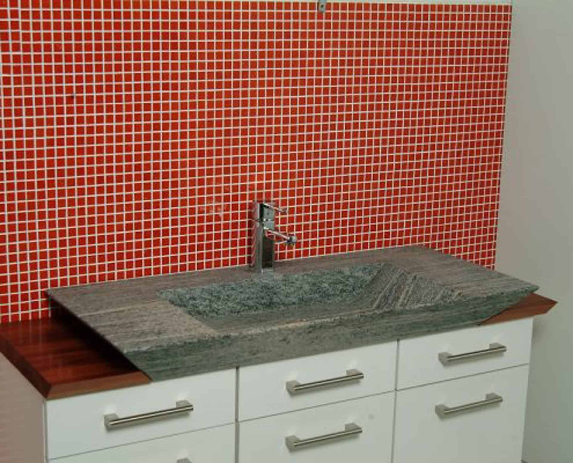 Eksklusiv designhåndvask fremstillet i massiv granit. Den røde granit har en mat finish. En ægte stenvask i målene: 60/80 x 35,5 x 10 cm. Vasken er bearbejdet ud af et helt stykke granit - vi fræser ganske enkelt en håndvask ud af sten. Alle de afsluttende små detaljer er håndlavet. Med denne vask vil man få et stykke natur hjem i badeværelset. Det er kvalitet, som holder mange år ud i tiden. Vasken kan bruges som fritstående vask - da vasken er flad i bunden er den velegnet til at placere direkte på en bordplade. Vasken er hensynsmæssigt designet med fine rundinger, som både giver vasken et eksklusivt udtryk og gør den rengøringsvenlig. Vasken vedligeholdes med voks - vi anbefaler en behandling med vores egen naturvoks ID12002 et par gange om året for at opnå optimalt look.