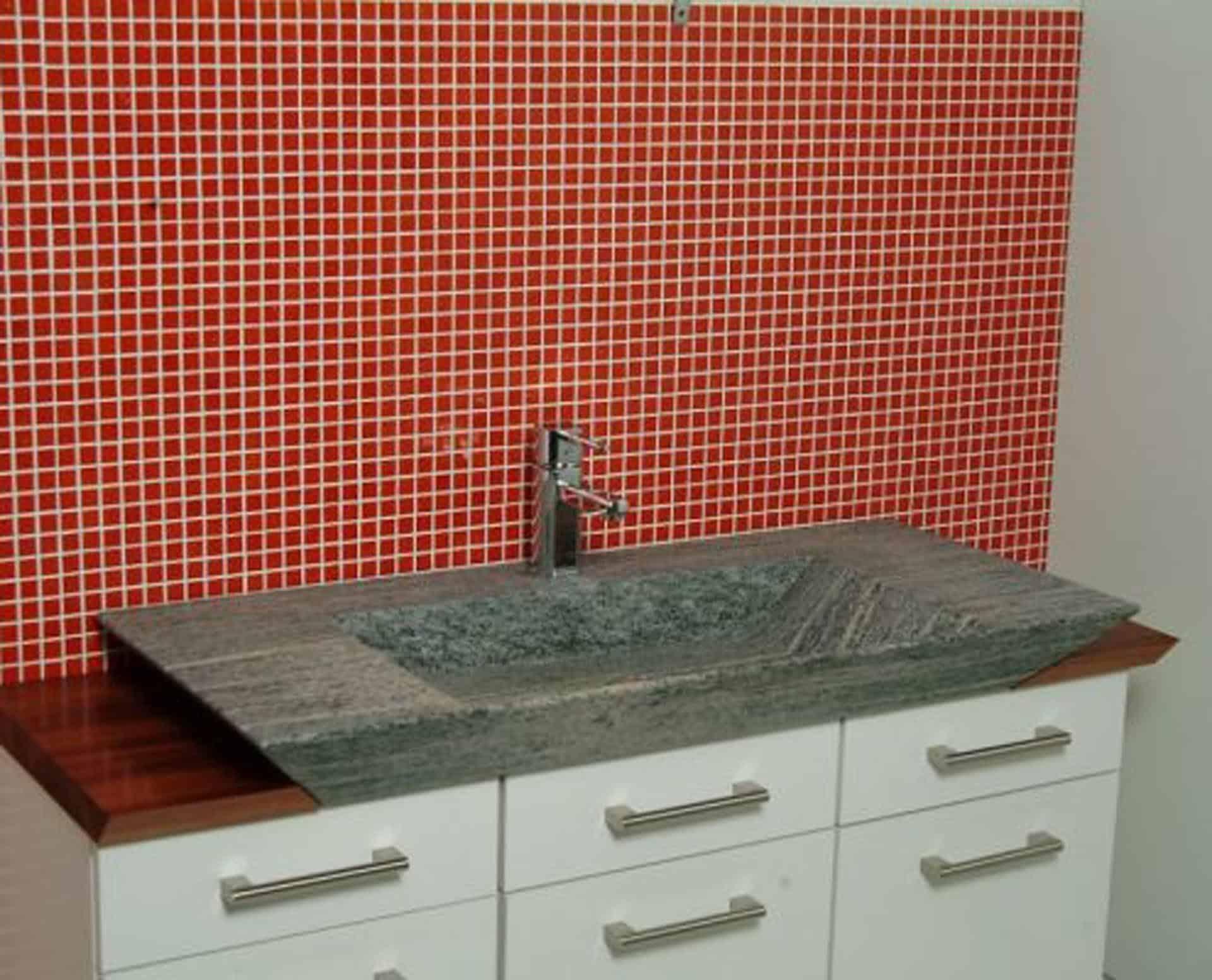 Eksklusiv designhåndvask fremstillet i massiv granit. Den røde granit har en mat finish. En ægte stenvask i målene: 80/100 x 35,5 x 10 cm. Vasken er bearbejdet ud af et helt stykke granit - vi fræser ganske enkelt en håndvask ud af sten. Alle de afsluttende små detaljer er håndlavet. Med denne vask vil man få et stykke natur hjem i badeværelset. Det er kvalitet, som holder mange år ud i tiden. Vasken kan bruges som fritstående vask - da vasken er flad i bunden er den velegnet til at placere direkte på en bordplade. Vasken er hensynsmæssigt designet med fine rundinger, som både giver vasken et eksklusivt udtryk og gør den rengøringsvenlig. Vasken vedligeholdes med voks - vi anbefaler en behandling med vores egen naturvoks ID12002 et par gange om året for at opnå optimalt look.