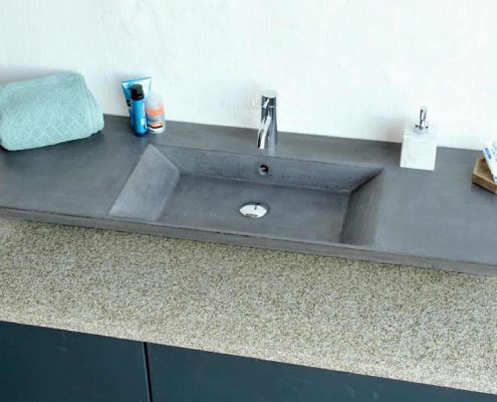 Lækker gnistret terrazzo håndvask, med pæne afrundinger. Farven er koksgrå med sorte og mørke sten - et råt look med en flot finish. Vasken har målene: 120/140 x 35,5 x 10 cm. Materialet er en blanding af cement og de små natursten der giver vasken sin flotte gnistrede finish. Vasken kan bruges som fritstående vask - da vasken er flad i bunden er den velegnet til at placere direkte på en bordplade. Vasken er hensynsmæssigt designet med fine rundinger, som både giver vasken et eksklusivt udtryk og gør den rengøringsvenlig. Vasken vedligeholdes med voks - vi anbefaler en behandling med vores egen naturvoks ID12002 et par gange om året for at opnå optimalt look.