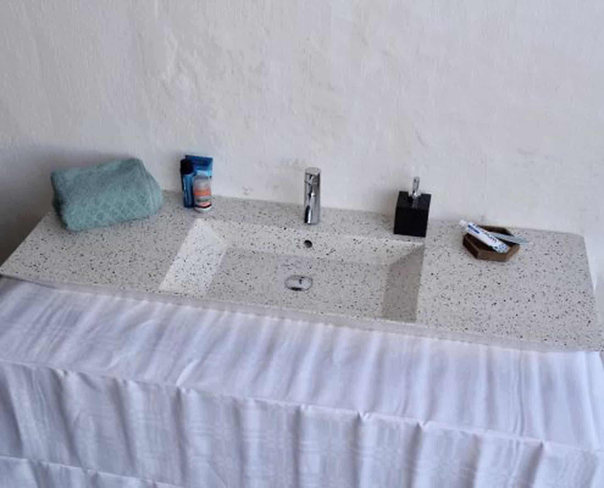 Lækker gnistret terrazzo håndvask, med pæne afrundinger. Farven er lys med sorte og mørke sten - et råt look med en flot finish. Vasken har målene: 120/140 x 35,5 x 10 cm. Materialet er en blanding af cement og de små natursten, der giver vasken sin flotte gnistrede finish. Vasken kan bruges som fritstående vask - da vasken er flad i bunden er den velegnet til at placere direkte på en bordplade. Vasken er hensynsmæssigt designet med fine rundinger, som både giver vasken et eksklusivt udtryk og gør den rengøringsvenlig. Vasken vedligeholdes med voks - vi anbefaler en behandling med vores egen naturvoks ID12002 et par gange om året for at opnå optimalt look.