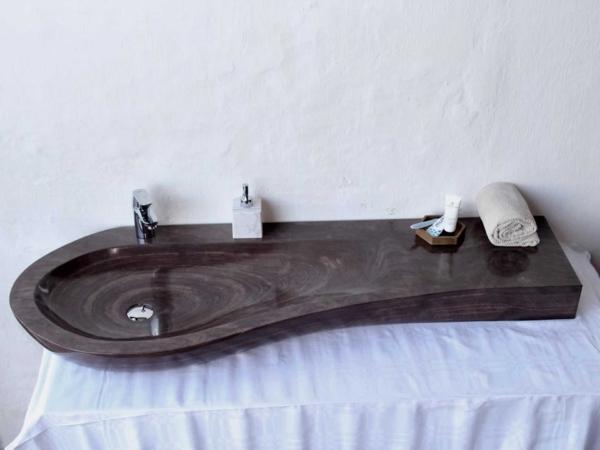 Eksklusiv designhåndvask fremstillet i massiv granit. Den har en mat finish og er i en beige/bordeaux farve, med struktur som træ - derfor kalder vi denne sten for woodline stone. En ægte stenvask i målene: 61 x 54 x 9,5 cm. Vasken er bearbejdet ud af et helt stykke granit - vi fræser ganske enkelt en håndvask ud af sten. Alle de afsluttende små detaljer er håndlavet. Med denne vask vil man få et stykke natur hjem i badeværelset. Det er kvalitet, som holder mange år ud i tiden. Vasken kan bruges som fritstående vask - da vasken er flad i bunden er den velegnet til at placere direkte på en bordplade. Vasken er hensynsmæssigt designet med fine rundinger, som både giver vasken et eksklusivt udtryk og gør den rengøringsvenlig. Vasken vedligeholdes med voks - vi anbefaler en behandling med vores egen naturvoks ID12002 et par gange om året for at opnå optimalt look.