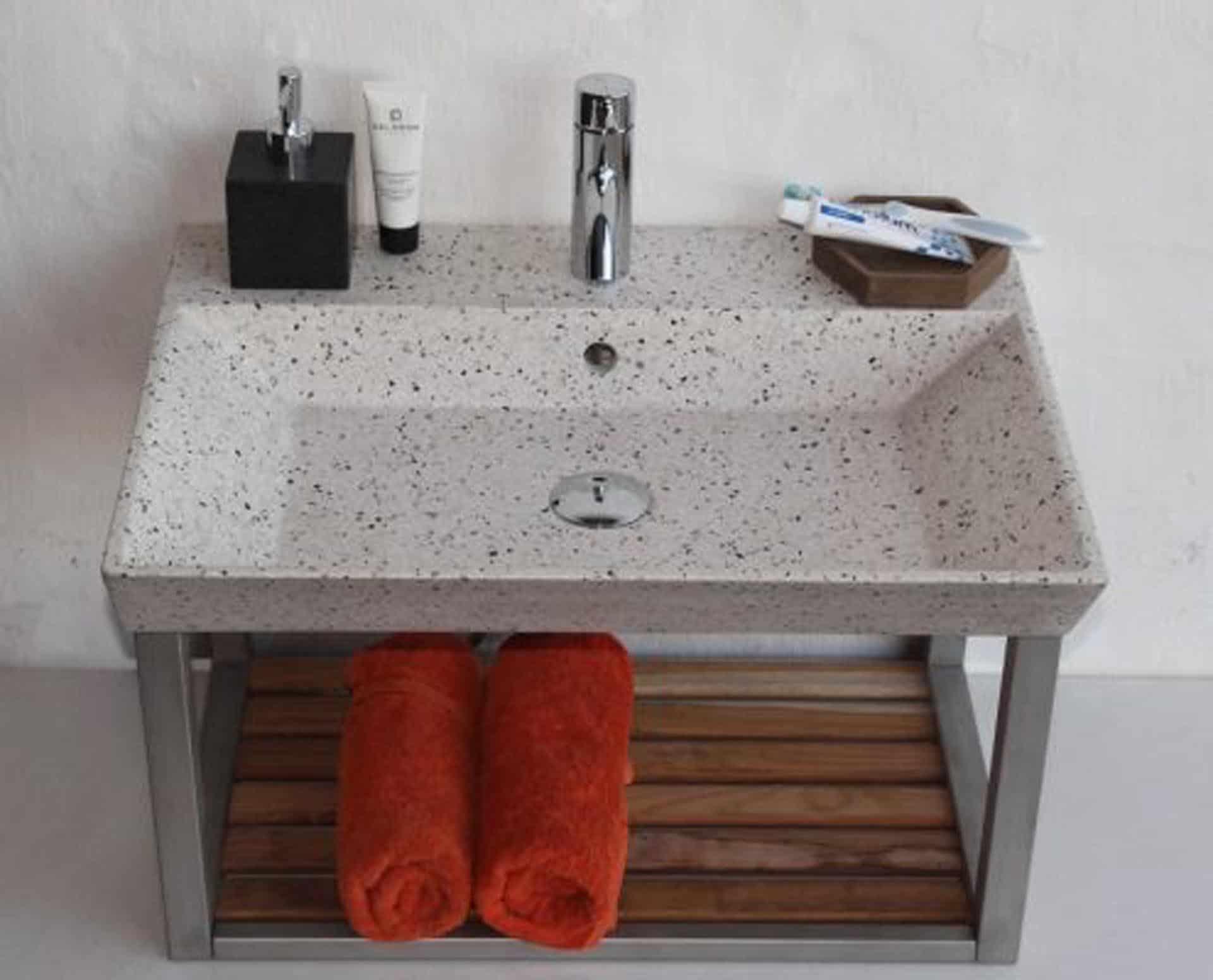 Lækker gnistret terrazzo håndvask, med pæne afrundinger. Farven er lys med sorte og mørke sten - et råt look med en flot finish. Vasken har målene: 60 x 35,5 x 10 cm. Materialet er en blanding af cement og de små natursten, der giver vasken sin flotte gnistrede finish. Vasken kan bruges som fritstående vask - da vasken er flad i bunden er den velegnet til at placere direkte på en bordplade. Vasken er hensynsmæssigt designet med fine rundinger, som både giver vasken et eksklusivt udtryk og gør den rengøringsvenlig. Vasken vedligeholdes med voks - vi anbefaler en behandling med vores egen naturvoks ID12002 et par gange om året for at opnå optimalt look.