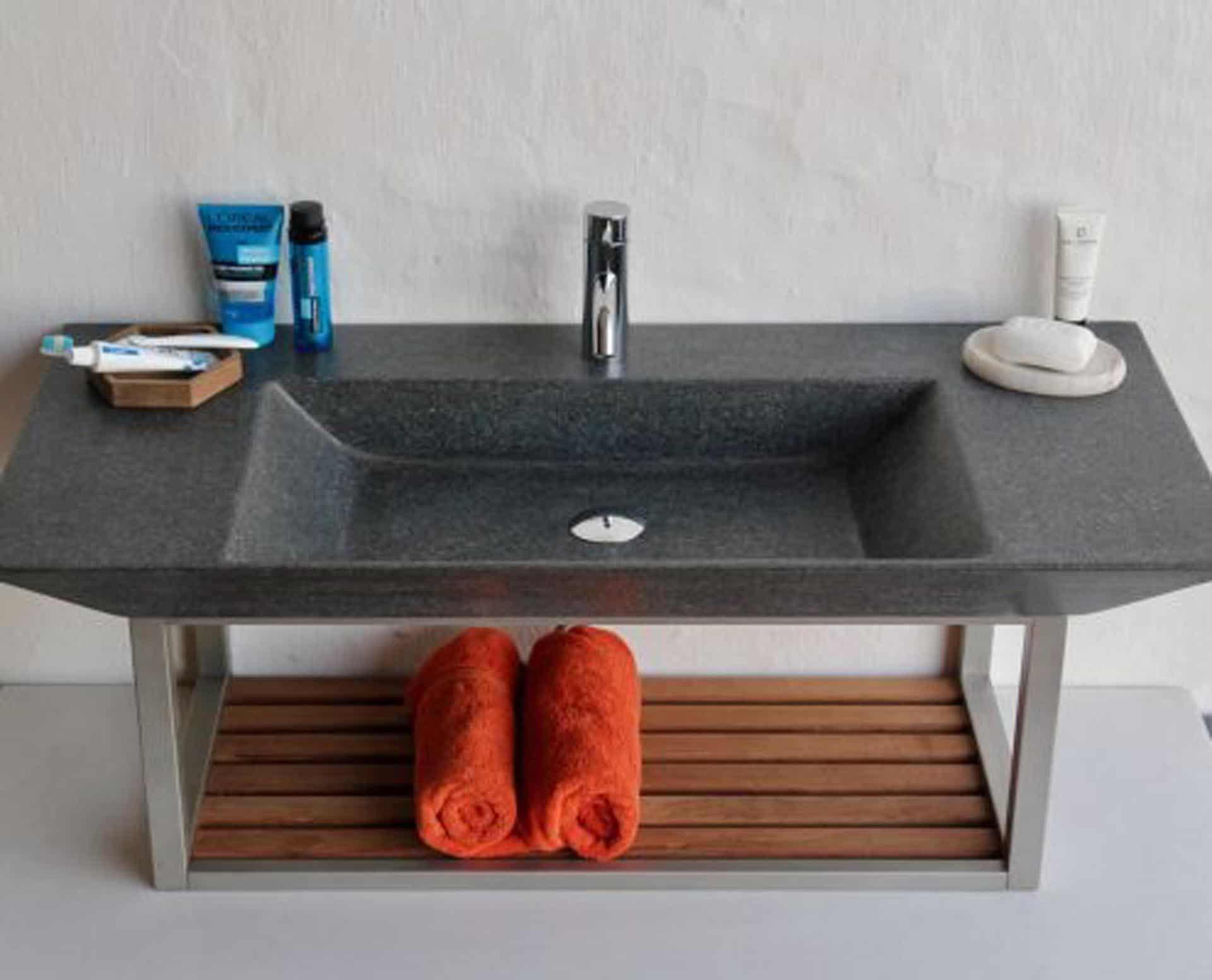 Eksklusiv designhåndvask fremstillet i massiv granit. Den sorte granit har en mat finish. En ægte stenvask i målene: 80/100 x 35,5 x 10 cm. Vasken er bearbejdet ud af et helt stykke granit - vi fræser ganske enkelt en håndvask ud af sten. Alle de afsluttende små detaljer er håndlavet. Med denne vask vil man få et stykke natur hjem i badeværelset. Det er kvalitet, som holder mange år ud i tiden. Vasken kan bruges som fritstående vask - da vasken er flad i bunden er den velegnet til at placere direkte på en bordplade. Vasken er hensynsmæssigt designet med fine rundinger, som både giver vasken et eksklusivt udtryk og gør den rengøringsvenlig. Vasken vedligeholdes med voks - vi anbefaler en behandling med vores egen naturvoks ID12002 et par gange om året for at opnå optimalt look.