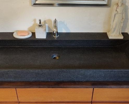Eksklusiv designhåndvask fremstillet i massiv granit. Den sorte granit har en mat finish. En ægte stenvask i målene: 123,2 x 50,5 x 9,5 cm. Vasken er bearbejdet ud af et helt stykke granit - vi fræser ganske enkelt en håndvask ud af sten. Alle de afsluttende små detaljer er håndlavet. Med denne vask vil man få et stykke natur hjem i badeværelset. Det er kvalitet, som holder mange år ud i tiden. Vasken kan bruges som fritstående vask - da vasken er flad i bunden er den velegnet til at placere direkte på en bordplade. Vasken er hensynsmæssigt designet med fine rundinger, som både giver vasken et eksklusivt udtryk og gør den rengøringsvenlig. Vasken vedligeholdes med voks - vi anbefaler en behandling med vores egen naturvoks ID12002 et par gange om året for at opnå optimalt look.